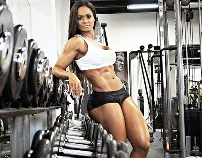 Denise Rodrigues leaning on a weight rack displaying her abs and glutes