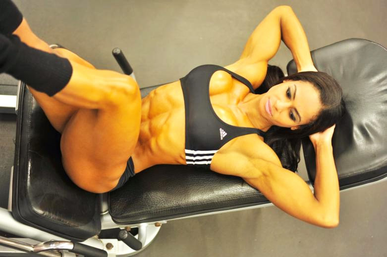Denise Rodrigues lying on a bench in the gym in sportswear