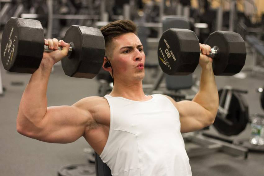 FaZe Censor doing a shoulder press exercise in the gym, wearing a sleeveless white shirt