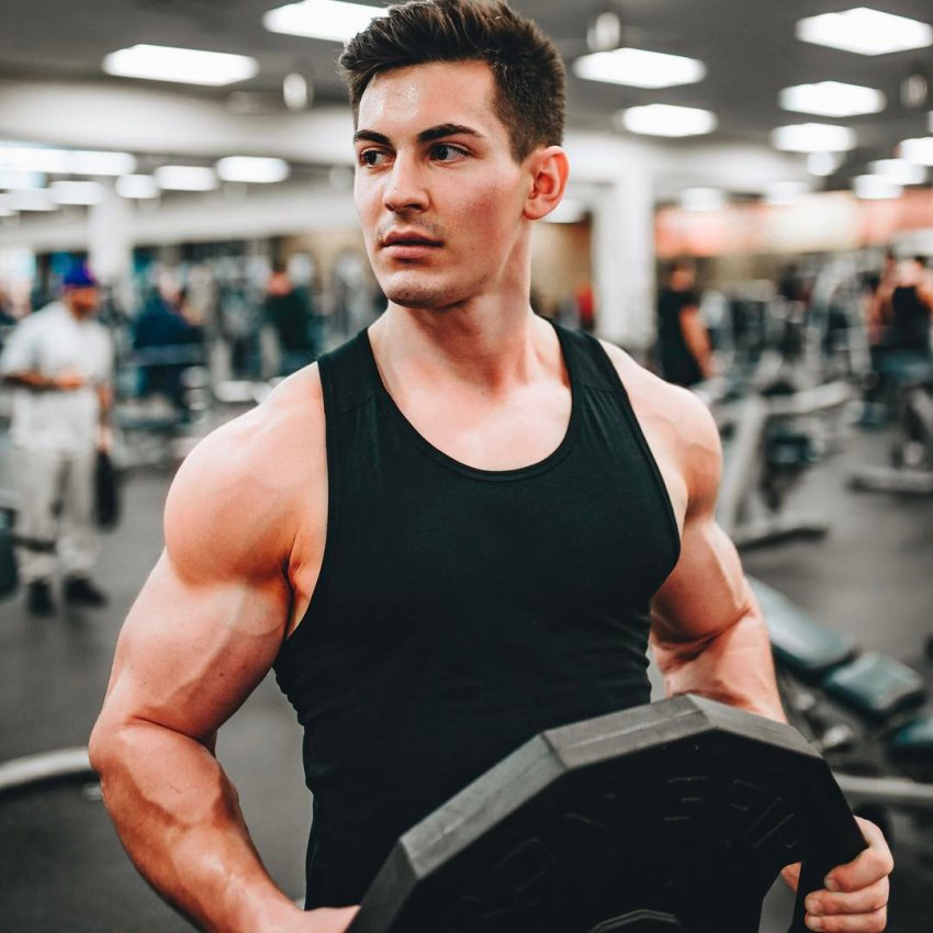 FaZe Censor holding a weight plate in the gym, wearing a black tank top, looking muscular and ripped