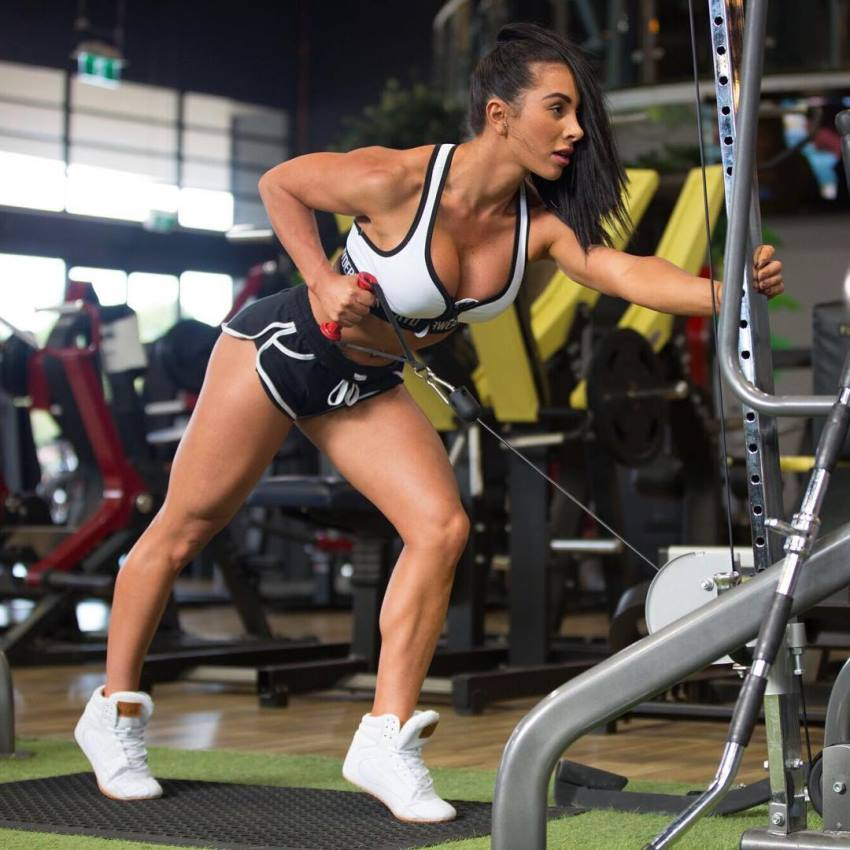 Giorgia Priscina doing a cable exercise in the gym, leaning forward, looking fit and lean