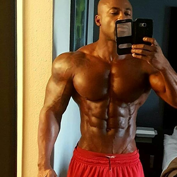 Jacques Lewis taking a selfie of his ripped abs, chest, arms, and shoulders