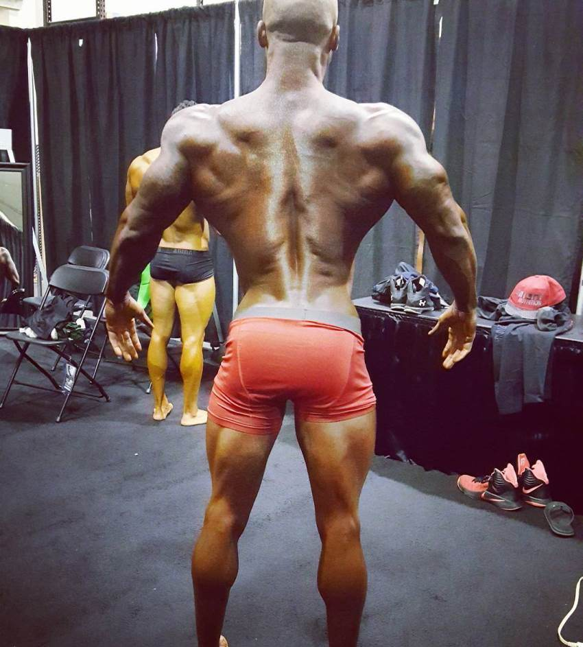 Jacques Lewis backstage, practicing his posing, showing his awesome back and legs