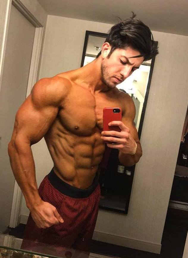 Jonny Bernstein taking a selfie of his flexed and ripped muscles in the mirror