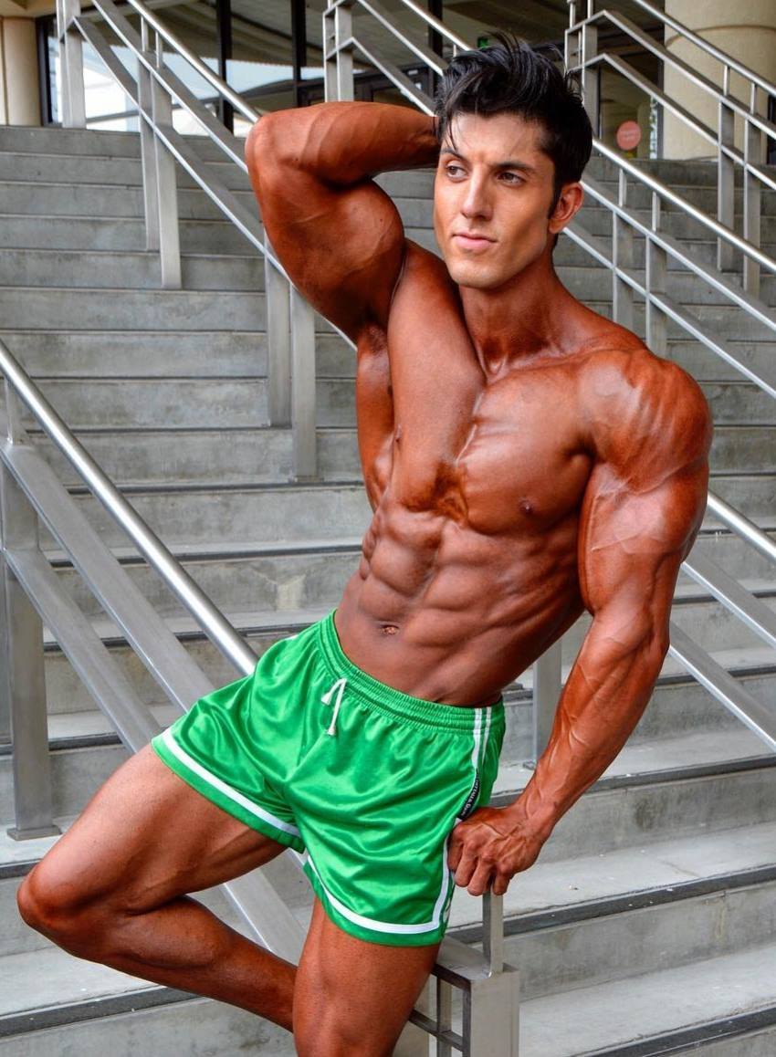 Jonny Bernstein wearing green shorts, tanned up, looking ripped and contest-ready