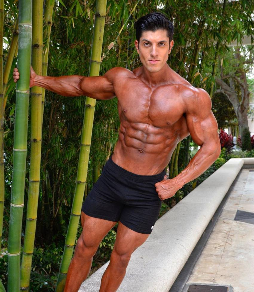 Jonny Bernstein hanging onto sugar cane, shirtless and tanned up, looking ripped and aesthetic