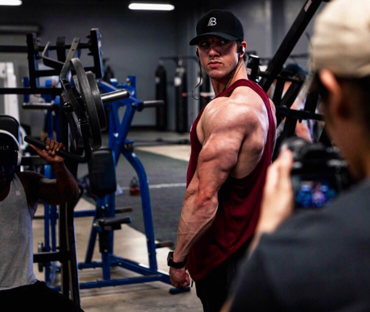 Jonny Bernstein wearing a red tank top, flexing his triceps and shoulders