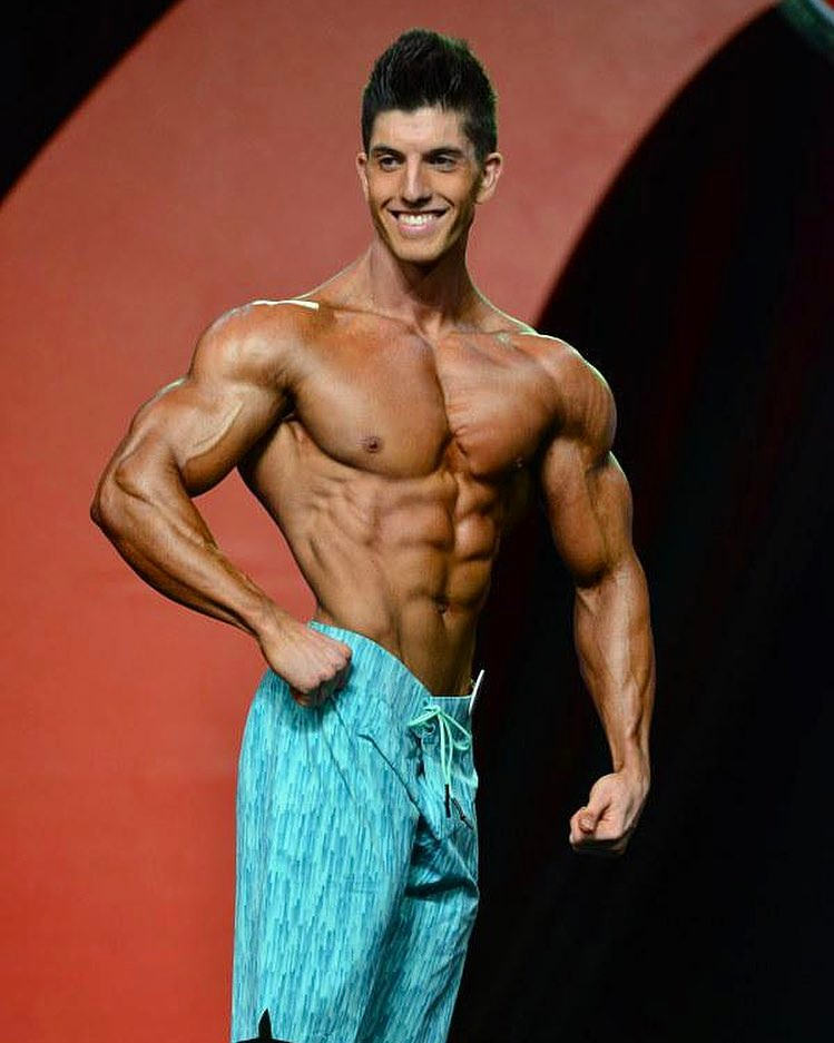 Jonny Bernstein on the Olympia stage in 2015, smiling at the judges and showing his conditioned physique