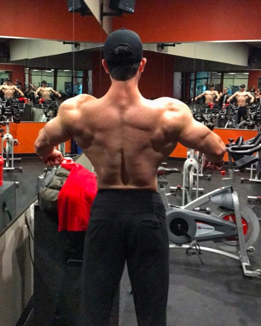 Shirtless Jonny Bernstein spreading his lats in the gym, showcasting his ripped back