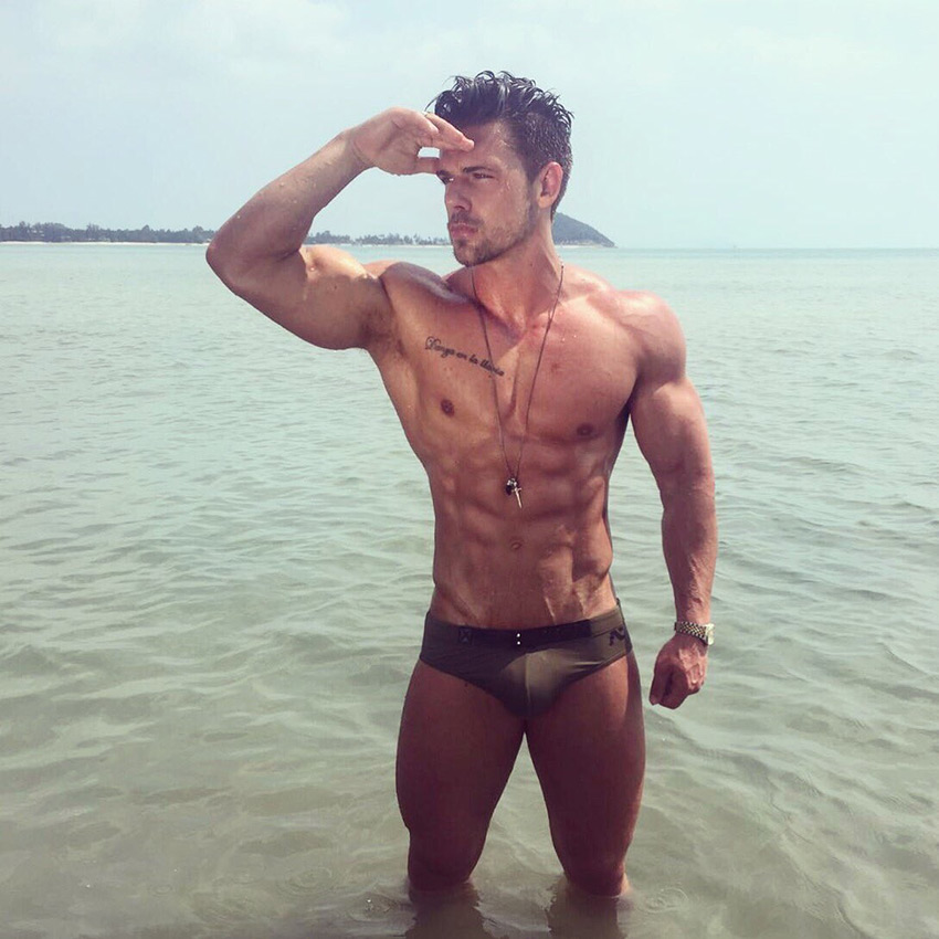 Joss Mooney standing in the ocean looking incredibly lean and ripped with a lean physique