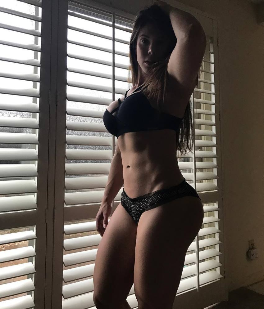 Juliana Barreto standing close to a window in a dark room, flexing her lean abs and legs
