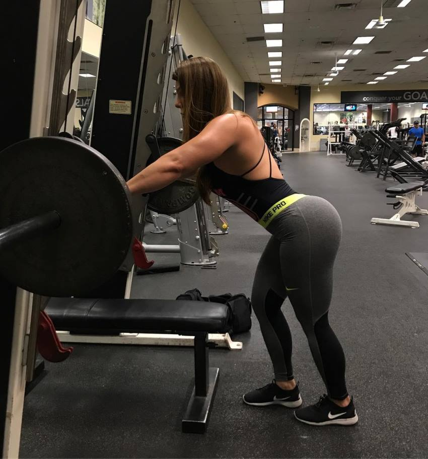 Juliana Barreto preparing to lift a barbell with weights in the gym