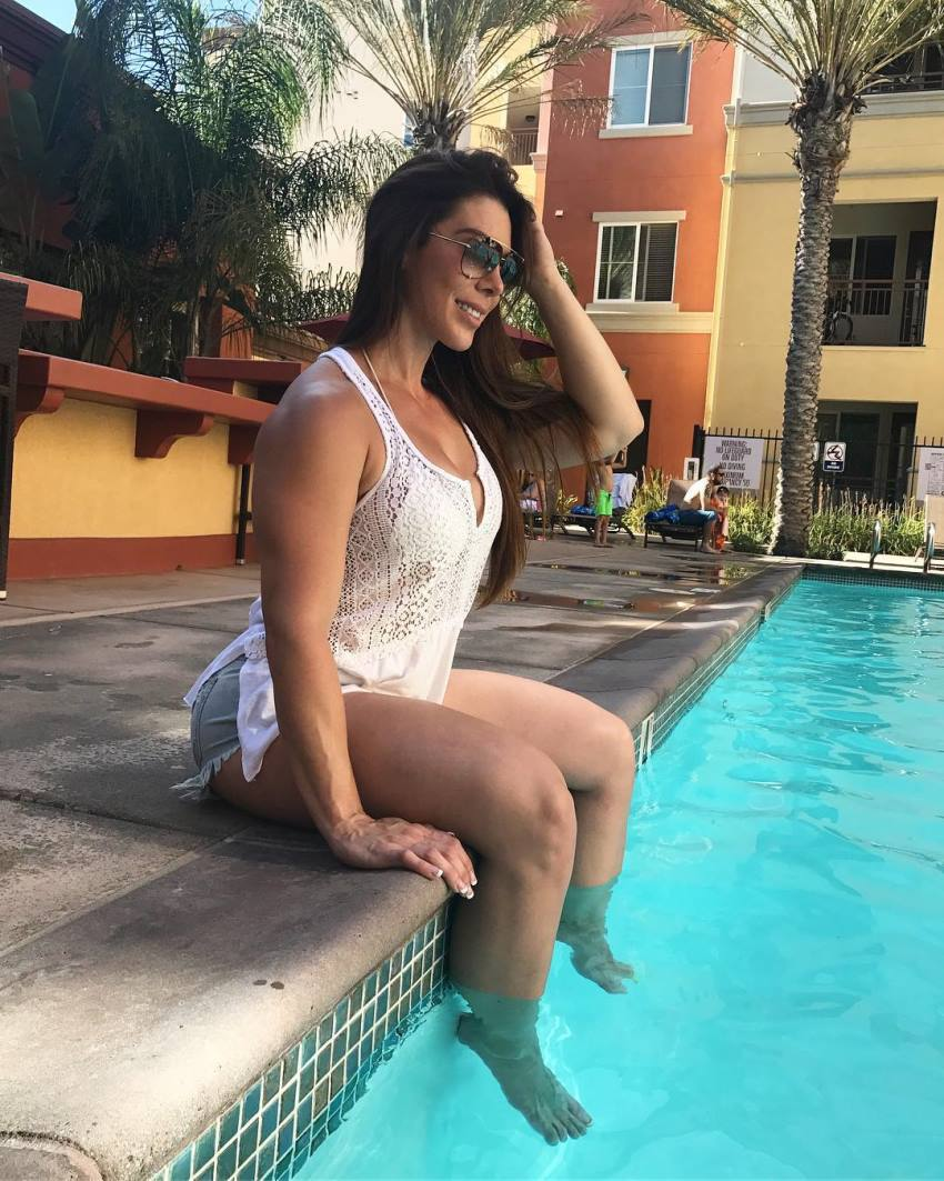 Juliana Barreto smiling and sitting by the pool with her legs in the water, looking lean and healthy