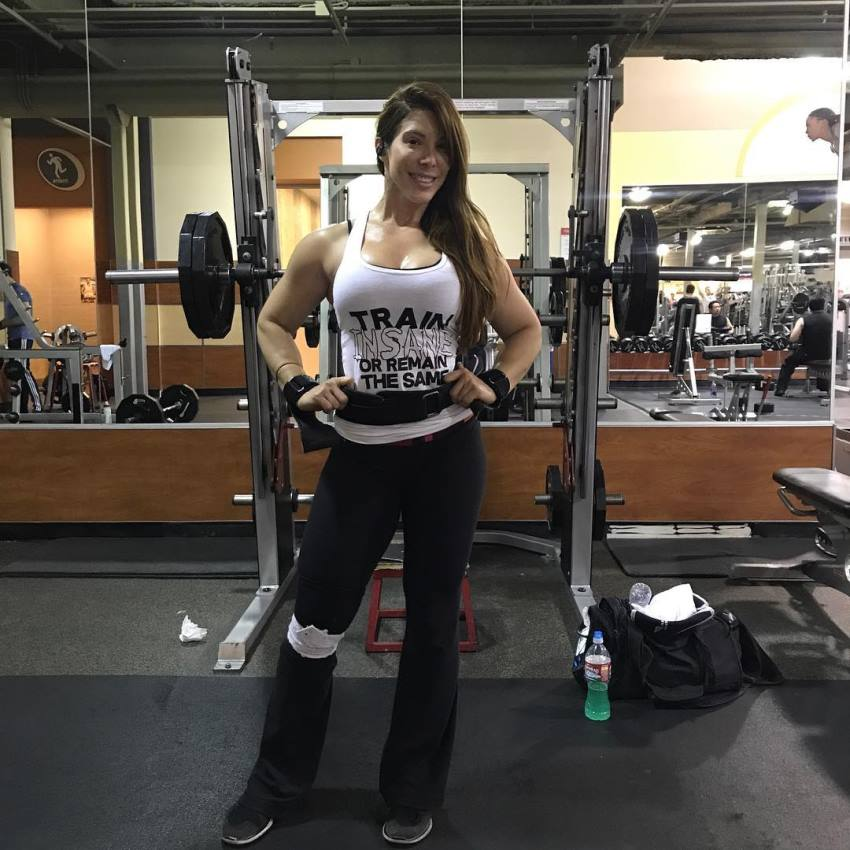 Juliana Barreto smiling at the camera, standing in front of a squat rack in the gym