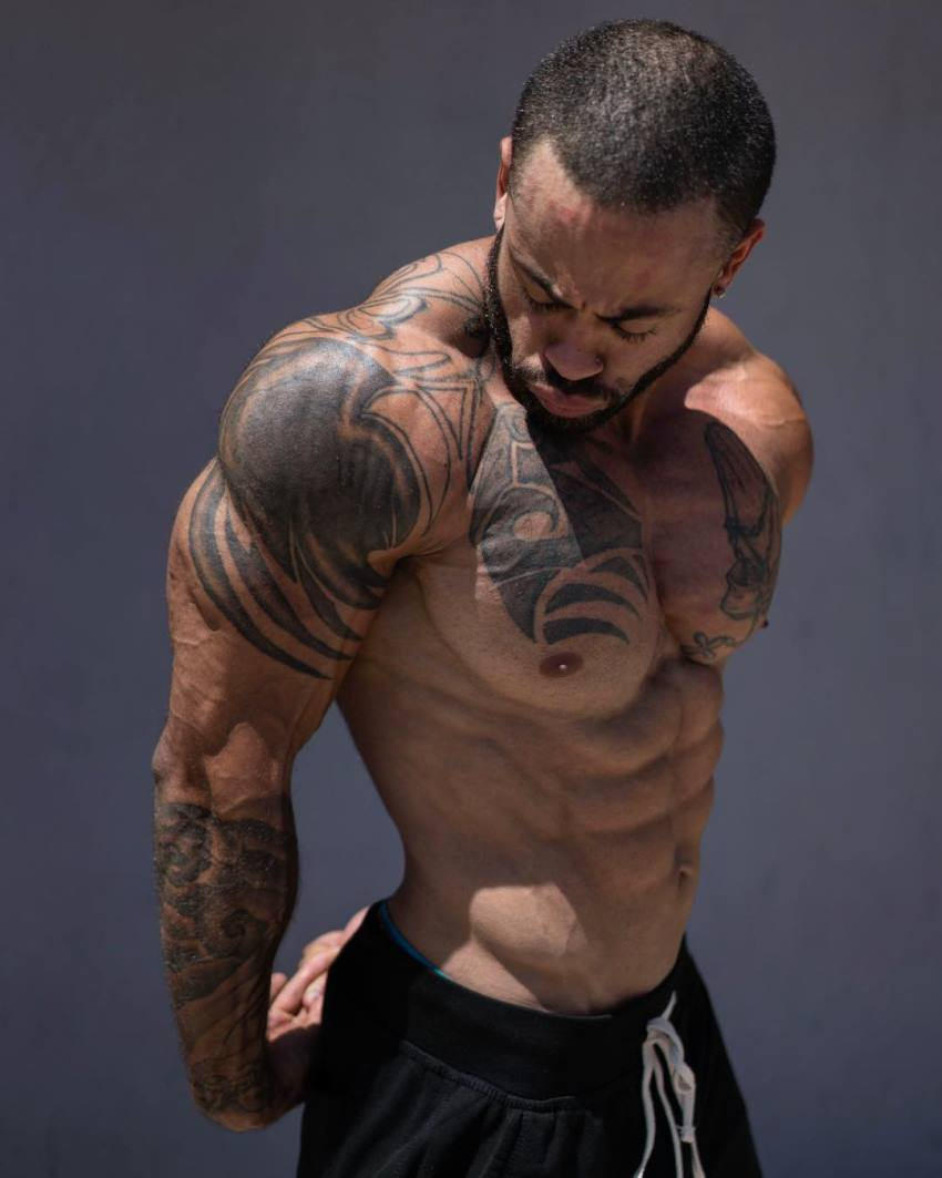 Kai Spencer flexing his triceps and shoulders, looking lean and muscular