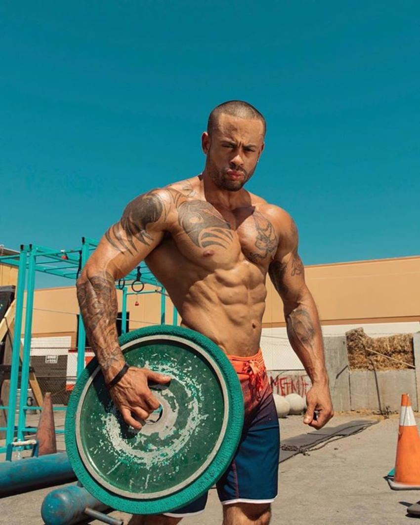 Kai Spencer holding a green weight plate, standing shirtless outdoors in the sun, looking fit and lean