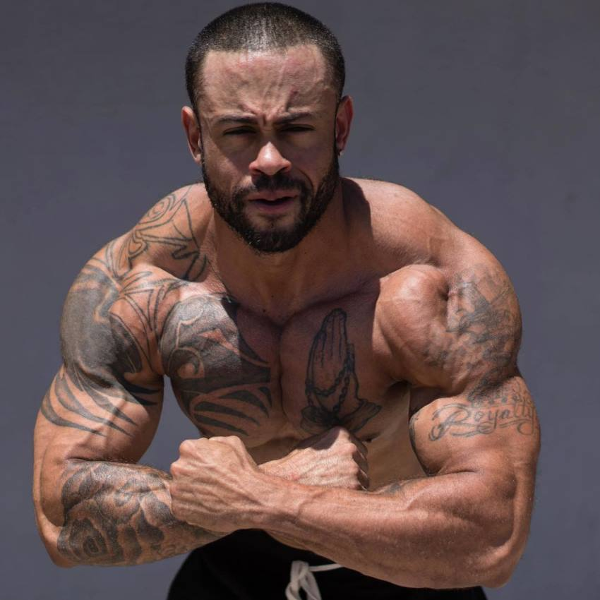 Kai Spencer doing the most muscular pose for the camera, looking ripped and aesthetic