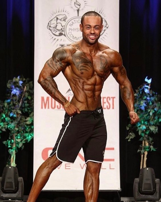 Kai Spencer displaying his conditioned and muscular physique on the Men's Physique bodybuilding stage
