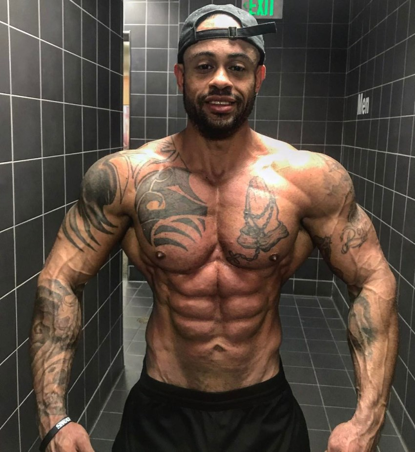 Kai Spencer spreading his arms and lats wide from the front, looking lean, ripped, and muscular