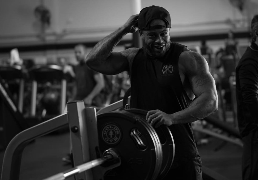Kai Spencer putting a weight plate on a bar in the gym, wearing a sleeveless shirt, looking muscular and fit