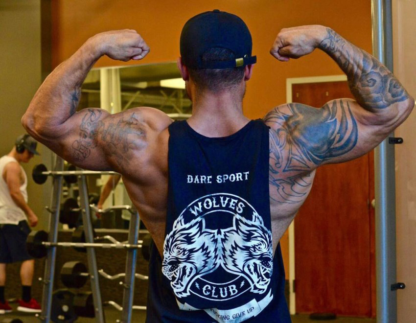 Kai Spencer doing a back double biceps pose in a sleeveless shirt, showcasting his ripped and muscular arms, shoulders, and back