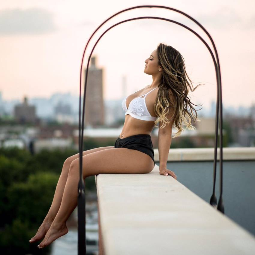 Laura Ivette sitting on a rooftop, looking lean and healthy