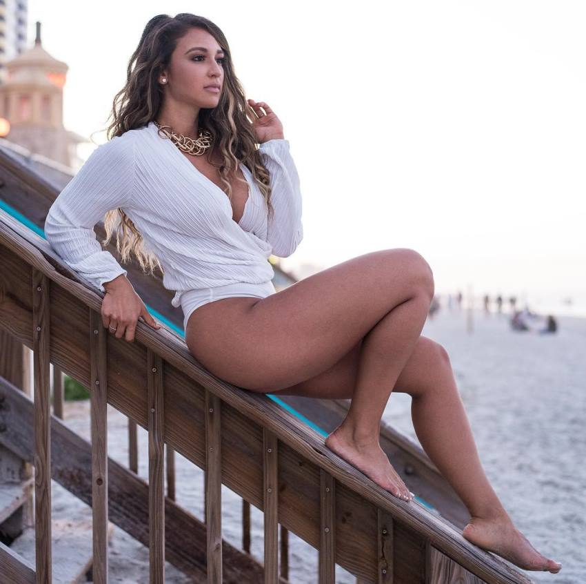 Laura Ivette lying on a construction by the beach, looking fit and aesthetic