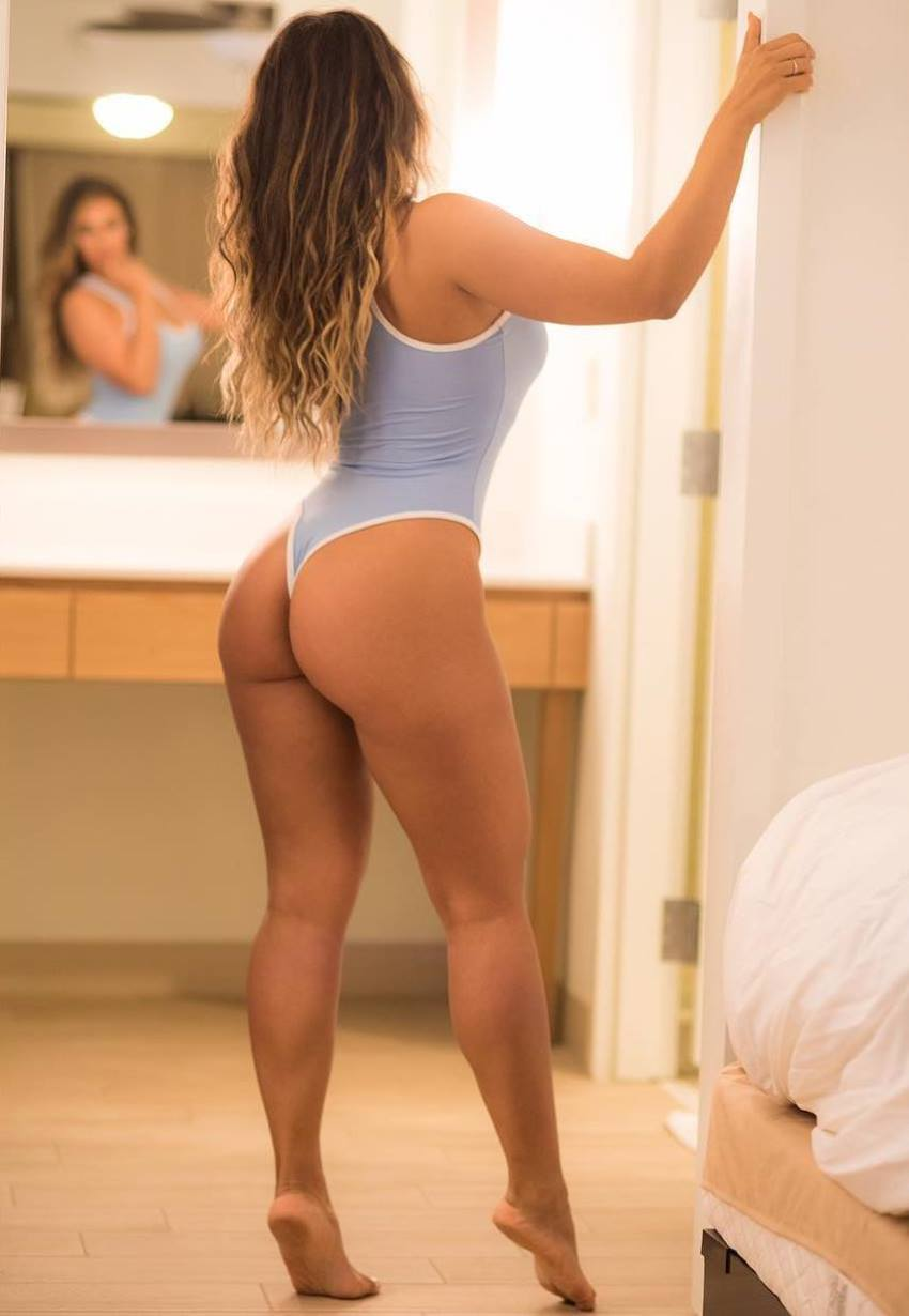 Laura Ivette looking at herself in the mirror, standing on her toes, her glutes and legs looking awesome