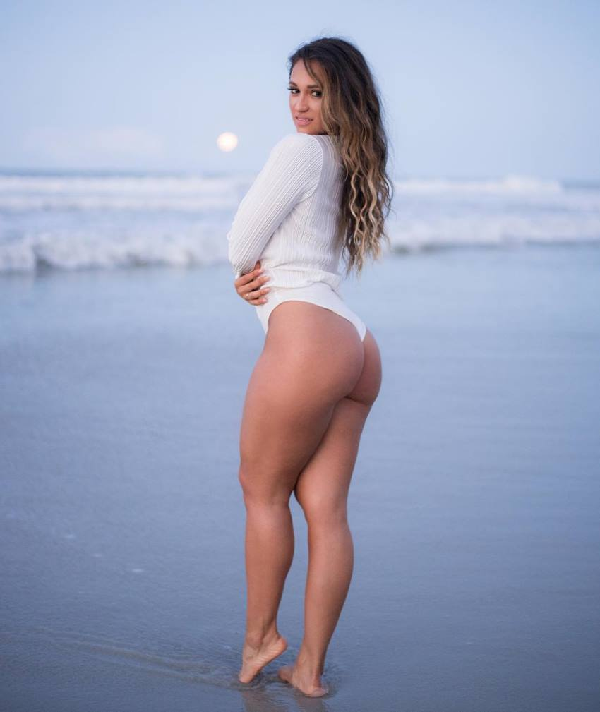 Laura Ivette standing on the shore in a revealing dress, showing her curvy legs and glutes