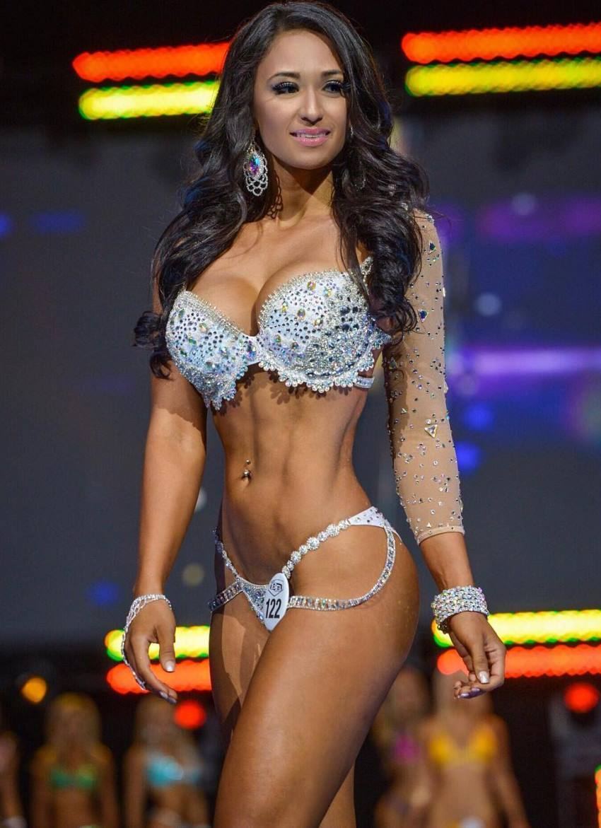 Laura Ivette standing on the WBFF stage, showing her awesome physique to the judges