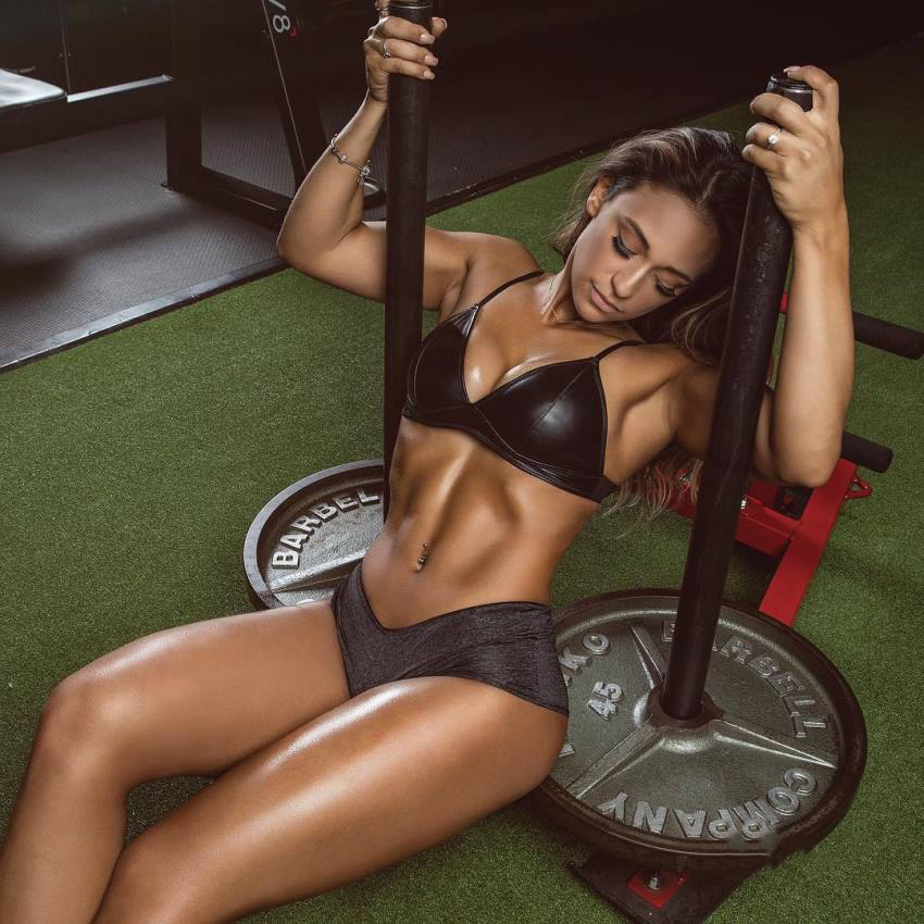 Laura Ivette sitting on a weighted card as a part of a photo shoot, displaying her ripped physique