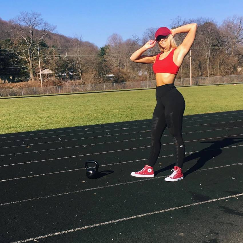 Leeci Knight standing outdoors with kettlebell on the ground, looking fit and healthy
