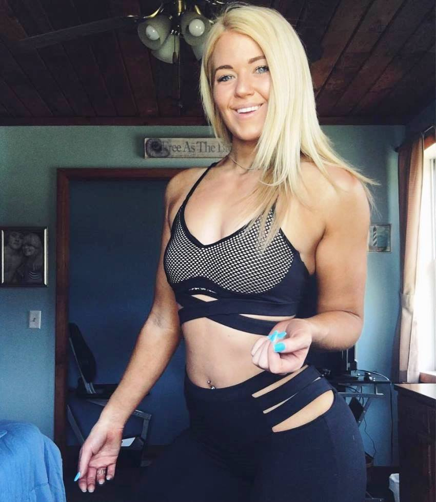 Leeci Knight posing for a picture, showing her fit abs and arms