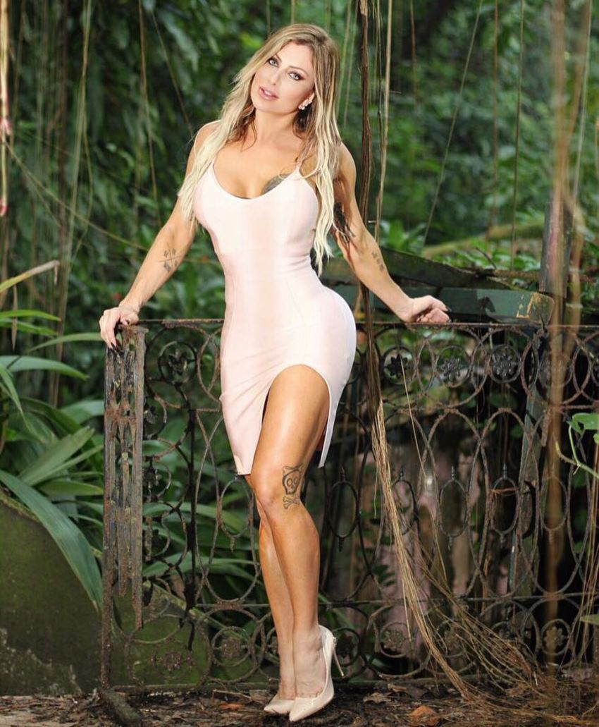Luciane Hoepers standing in the woods in her silky dress, looking fit and lean