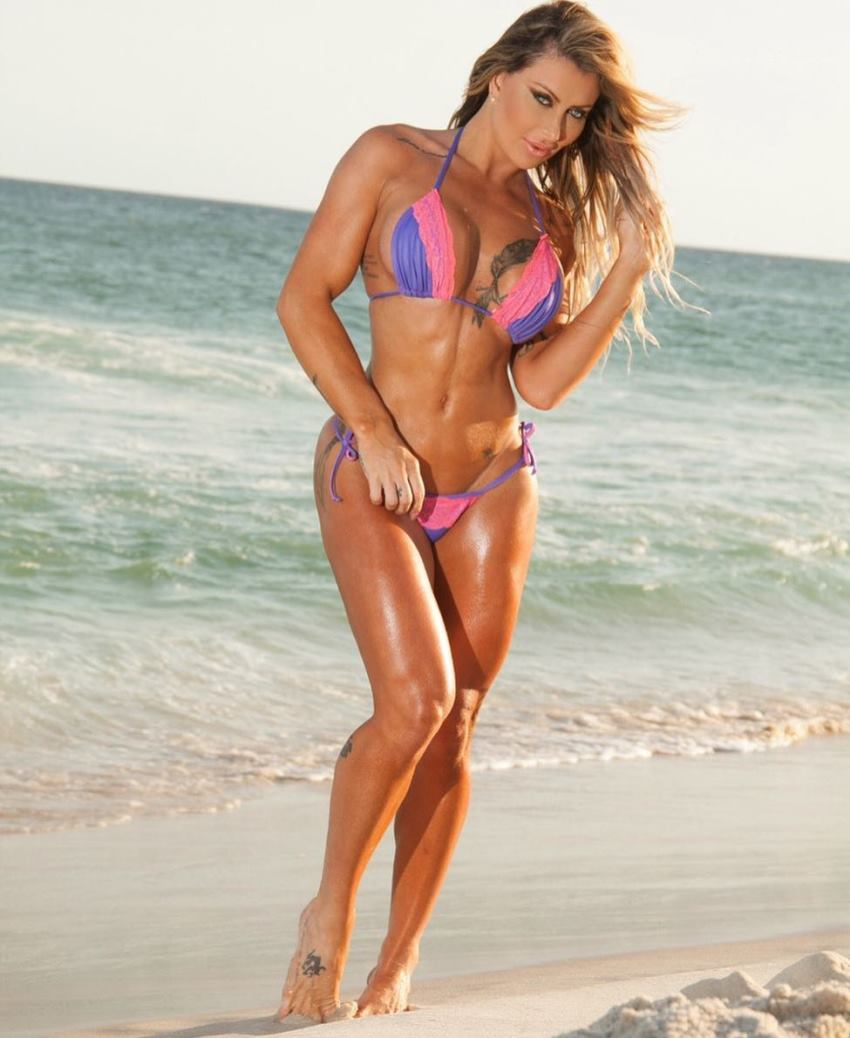 Luciane Hoepers standing on the beach, flexing her lean abs and legs