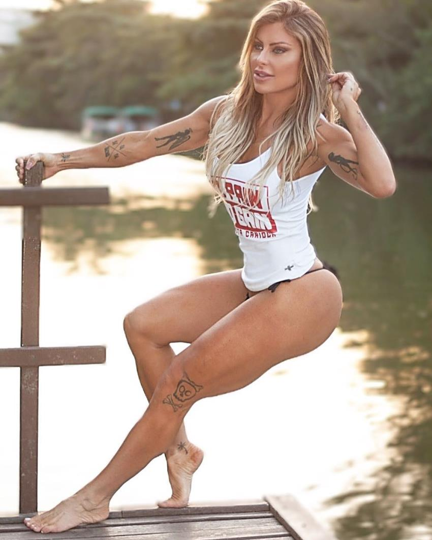 Luciane Hoepers posing by a beautiful green river, looking lean, fit, and healthy