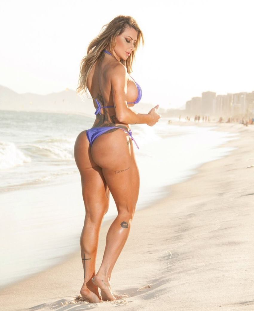 Luciane Hoepers standing on the beach in a blue bikini, revealing her awesome glutes and legs