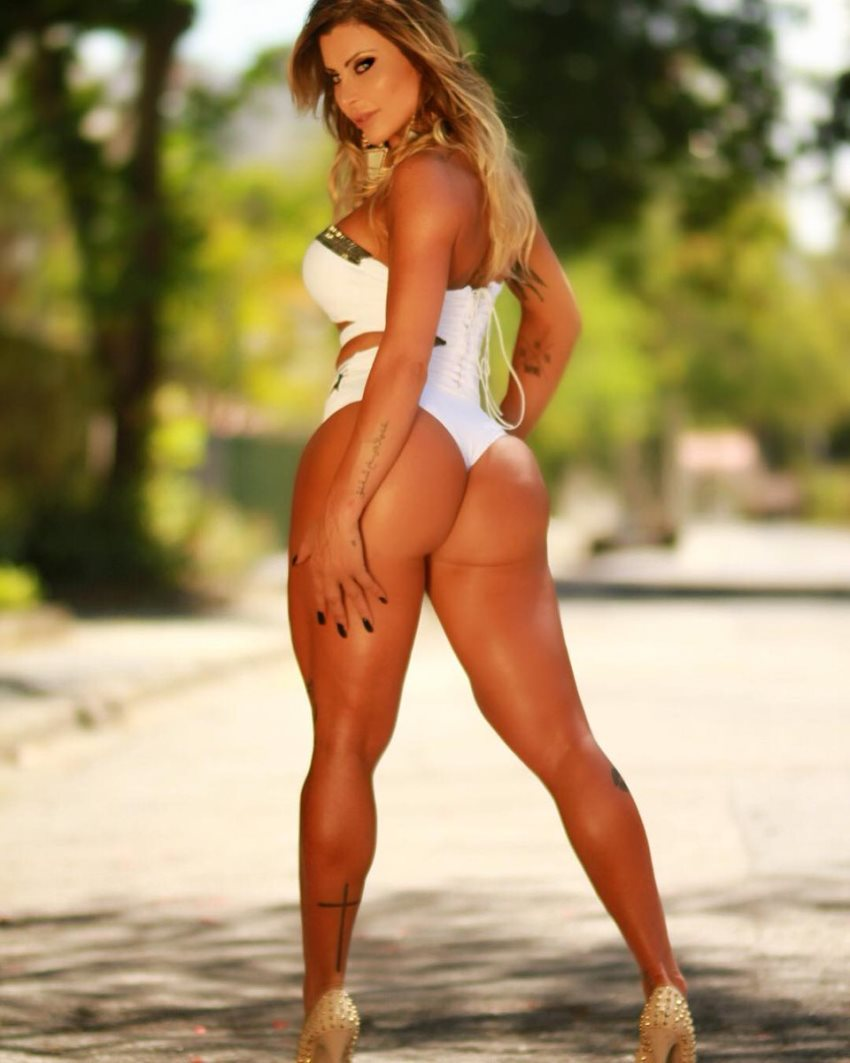 Luciane Hoepers standing in a shade on a sunny day, displaying her awesome glutes and legs