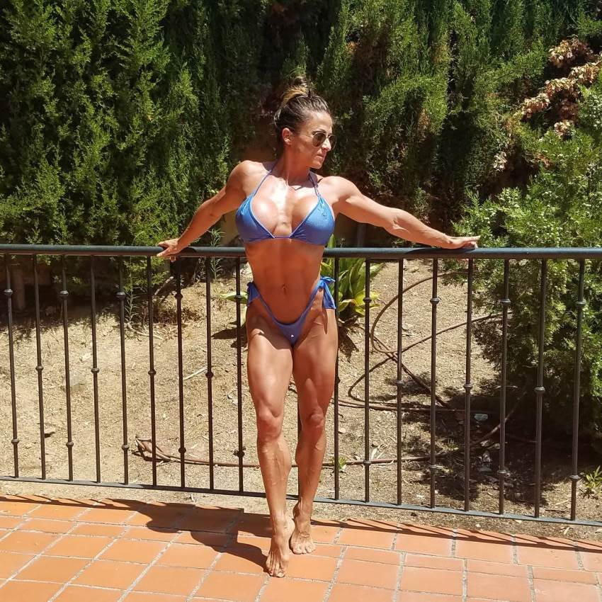 Maria Garcia in a blue bikini enjoying the sun on a balcony, with green pine trees behind her, looking fit and healthy