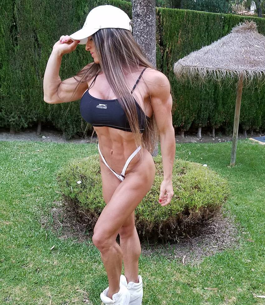 Maria Garcia standing outdoors, her abs, legs and arms looking extremely ripped and aesthetic