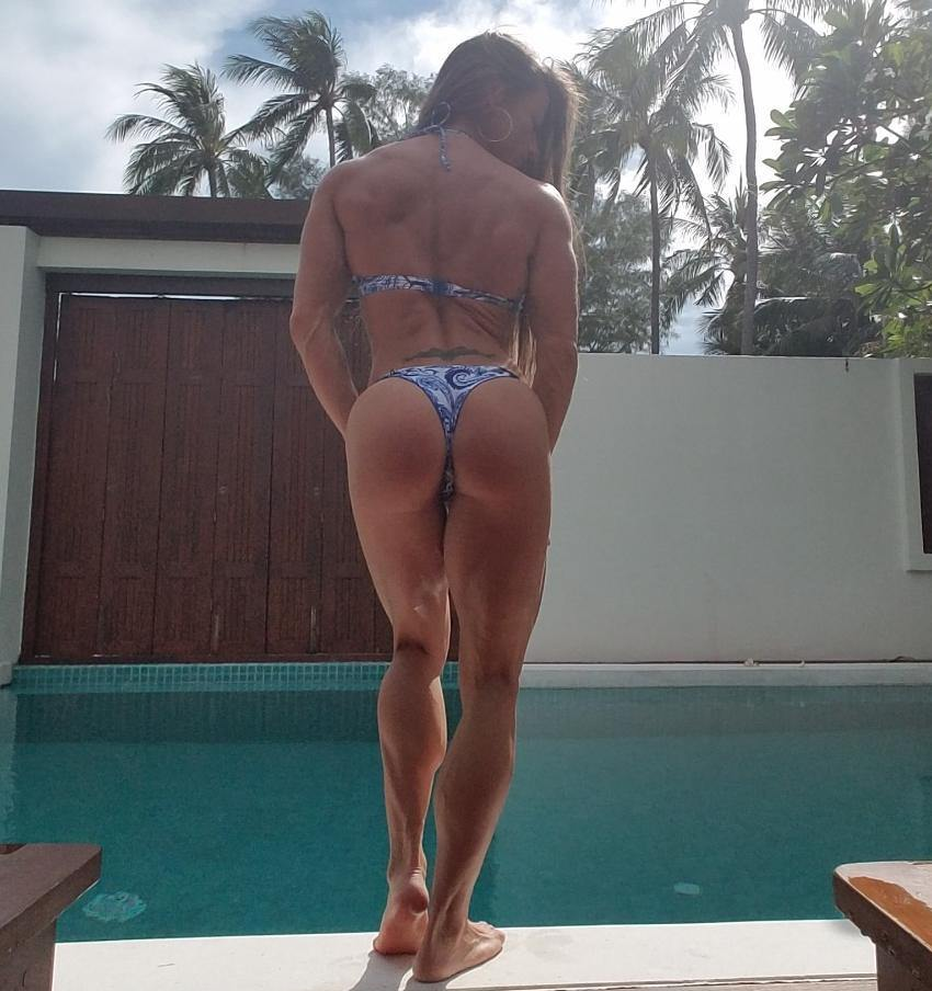 Maria Garcia standing by the pool in a bikini, showing her back, legs, and glutes, looking lean and muscular