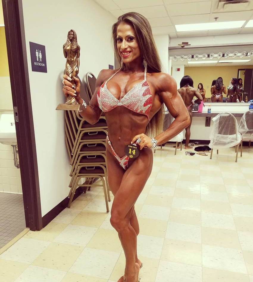 Maria Garcia posing for a photo with a statue trophy in her hand, smiling, and looking awesome