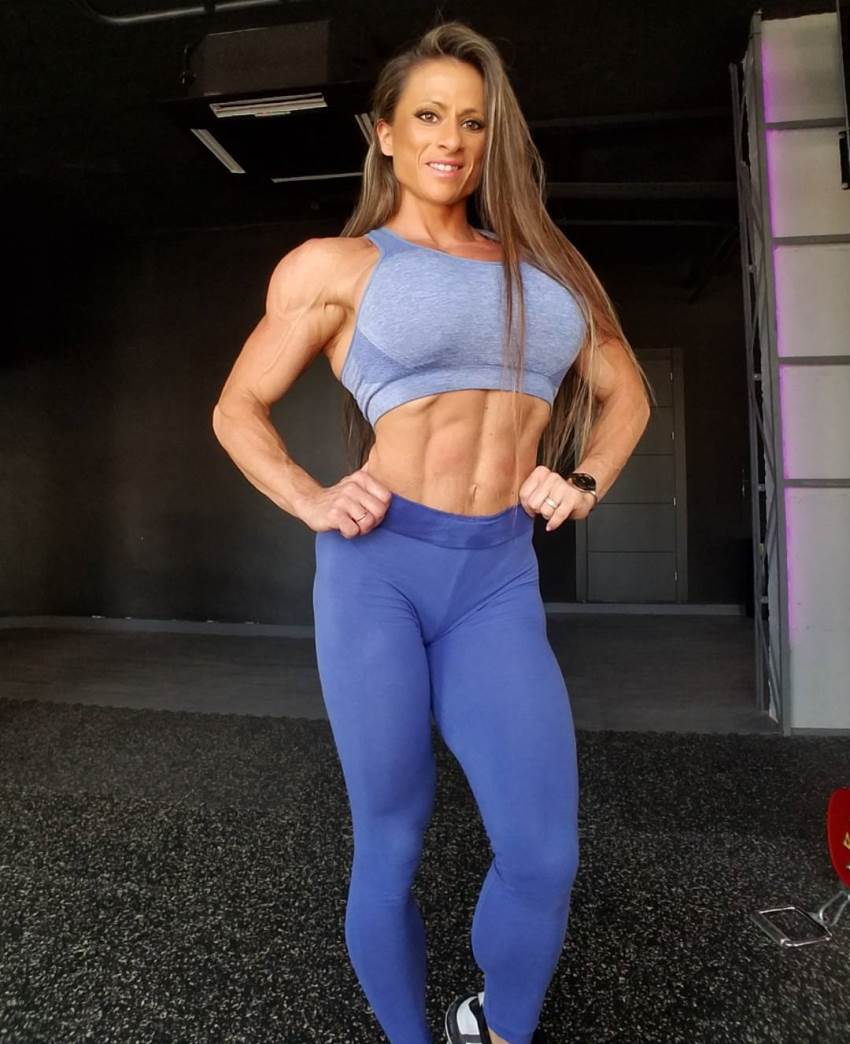 Maria Garcia posing for a photo in light blue gym wear, her abs looking fit and toned