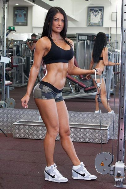 Marika Magriplis in a photo shoot in the gym holding a cable looking muscular