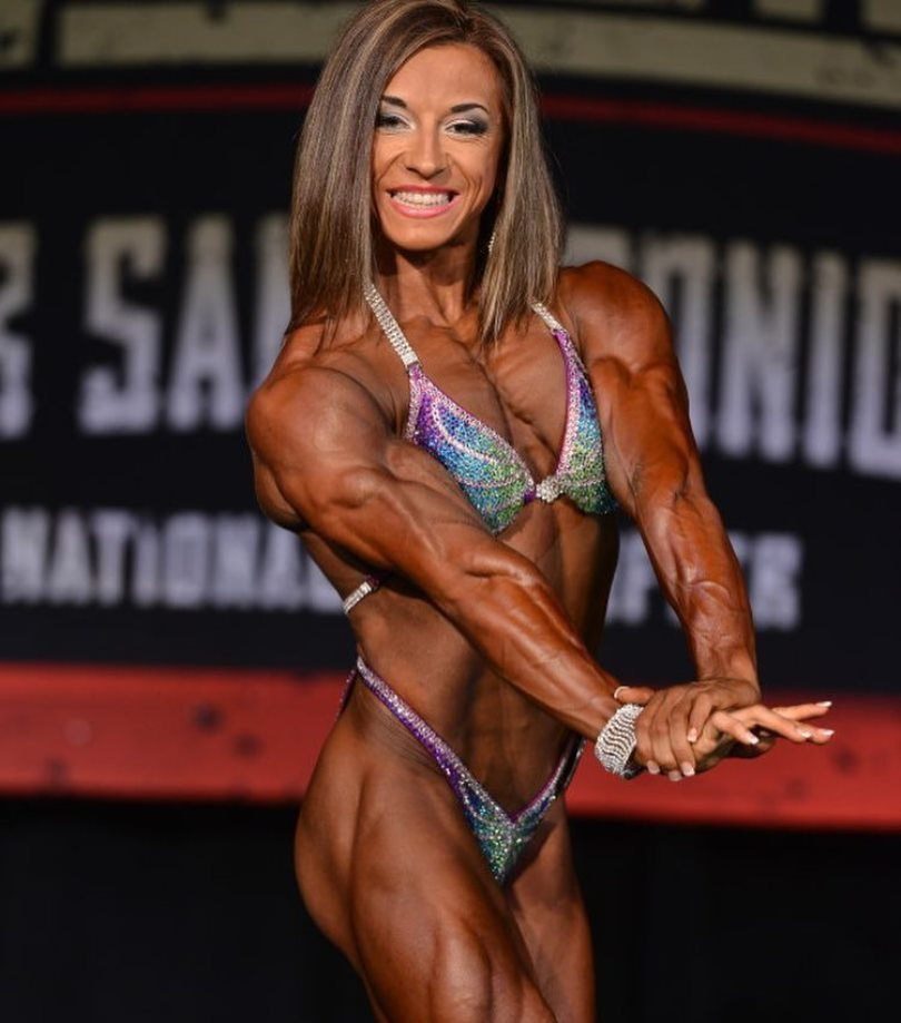 Michaela Aycock flexing her triceps on the stage, looking ripped and muscular