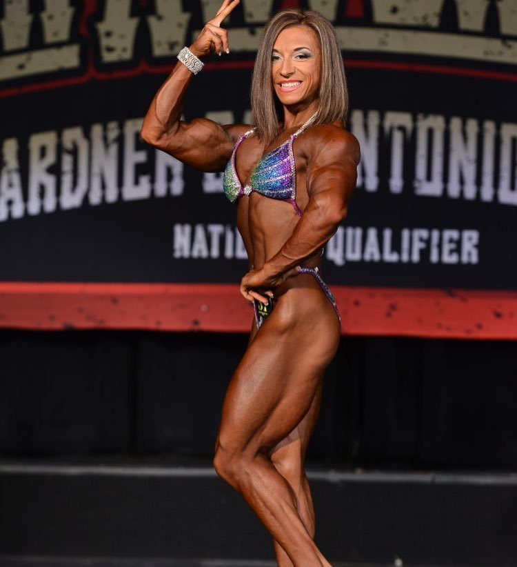Michaela Aycosk flexing her biceps and legs on the stage, looking extremely lean and aesthetic