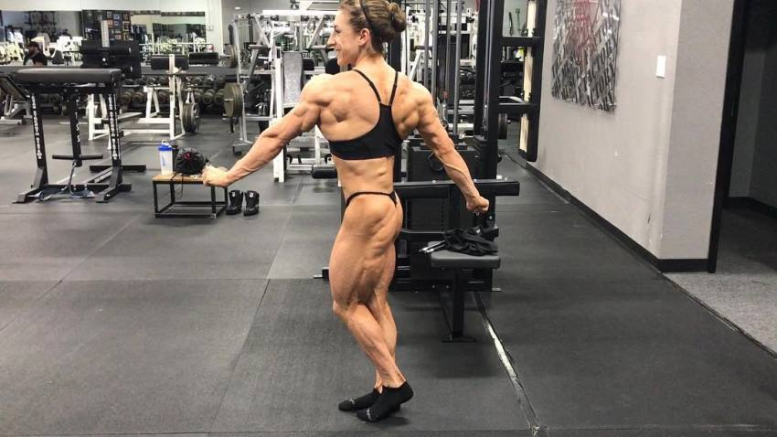 Michaela Aycock practicing posing in the gym, looking muscular and lean