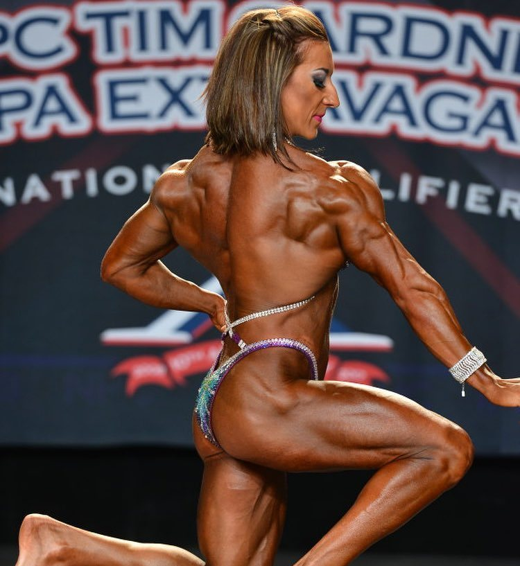Michaela Aycock performing a pose on the stage, showing her ripped back, legs, arms, and glutes