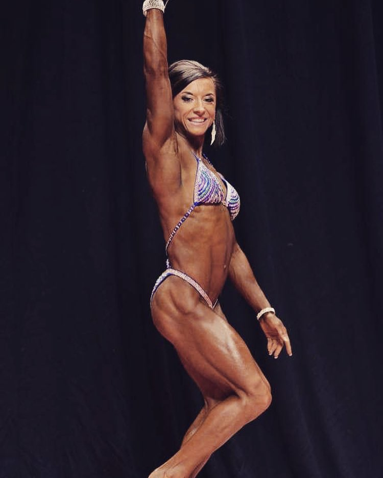 Michaela Aycock waving to the audience on the stage, looking conditioned and muscular