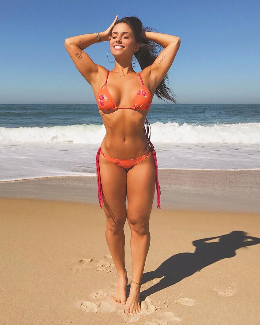 Thamires Hauch stretching in the sun on the beach in her bikini